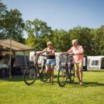 kamperend-stel-met-fietsen-aan-de-hand