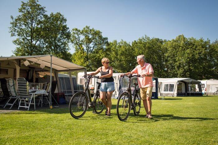 kamperend stel met fietsen aan de hand